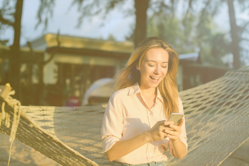 Young happy woman using smartphone and sitting in wicker hammock on tropical resort.